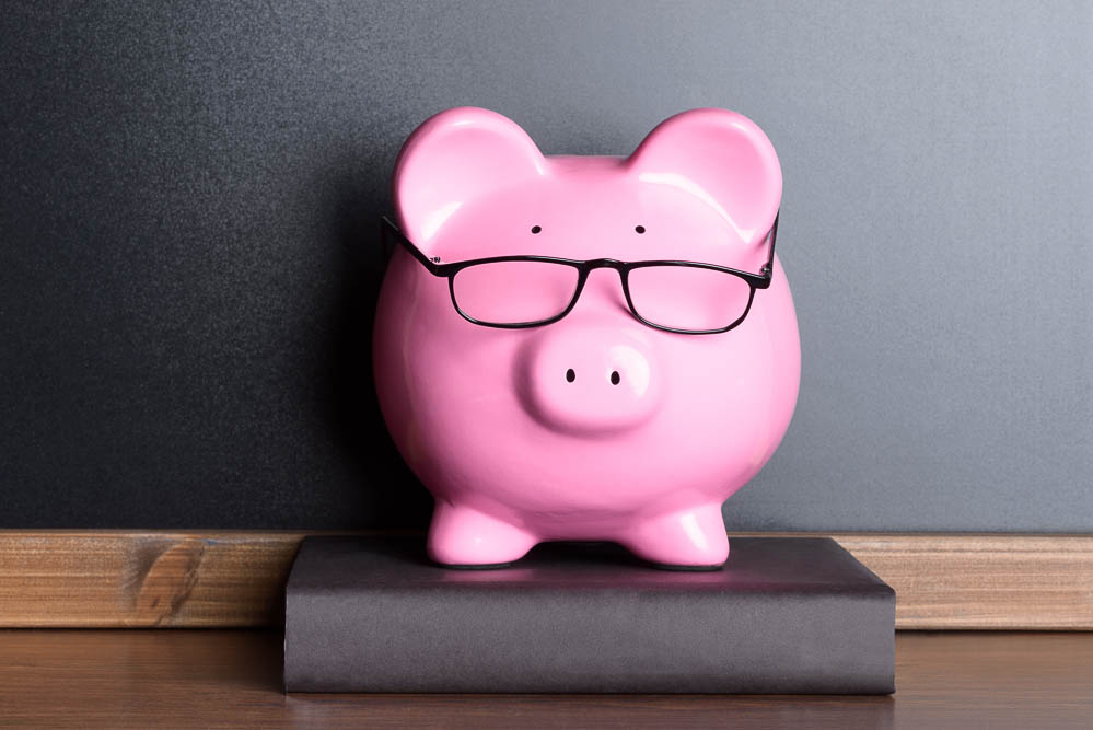 Pink Piggy Bank With Eye Glasses On Book Near Blackboard